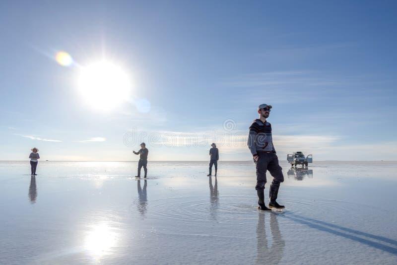 Les touristes heureux apprécient des activités de visite de jeep dans le lac plat Salar de Uyuni salt en Bolivie image stock