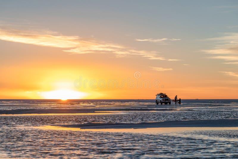 Les touristes heureux apprécient le coucher du soleil pendant la visite à quatre roues dans le lac plat Salar de Uyuni salt en Bo images libres de droits