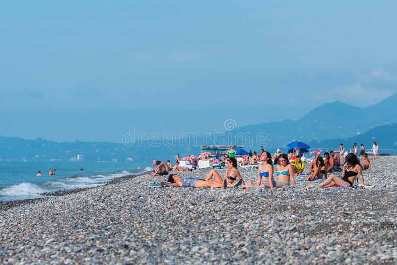 Les touristes (jeunes femmes) les prennent un bain de soleil sur la plage de Batumi images stock