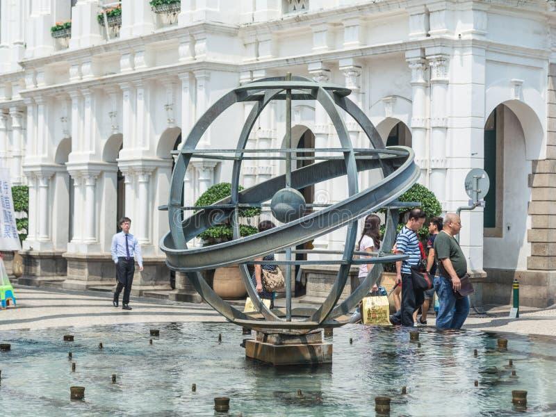 Les touristes marchent passage la statue de globe en métal dans la fontaine à la place de Senado dans Macao, Chine photos stock