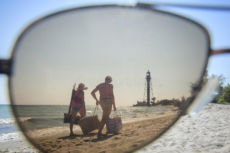 Les touristes marchent sur la plage de mer Dans la distance vous pouvez voir le vieux phare photo libre de droits