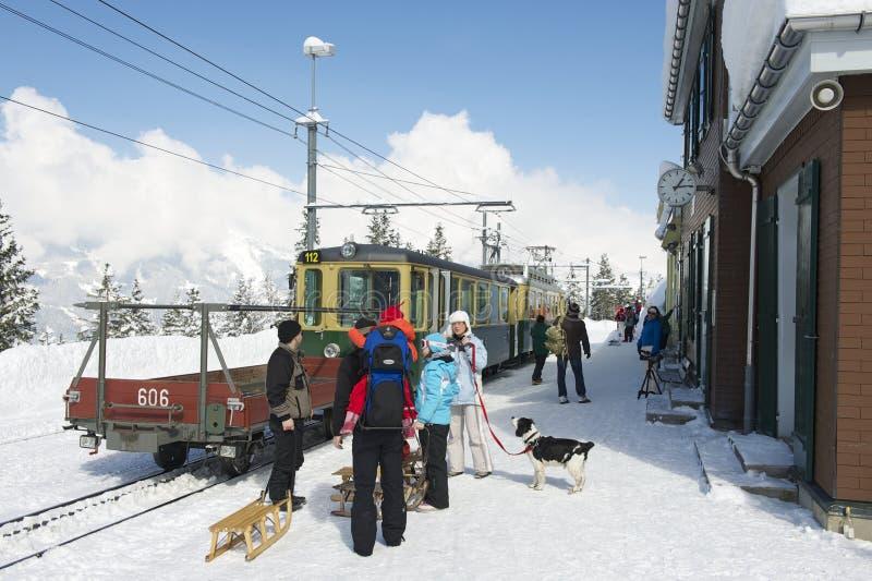 Les touristes non identifiés avec des klaxon-traîneaux attendent le train à la station de train de Wengernalpbahn dans Grindelwal photo libre de droits