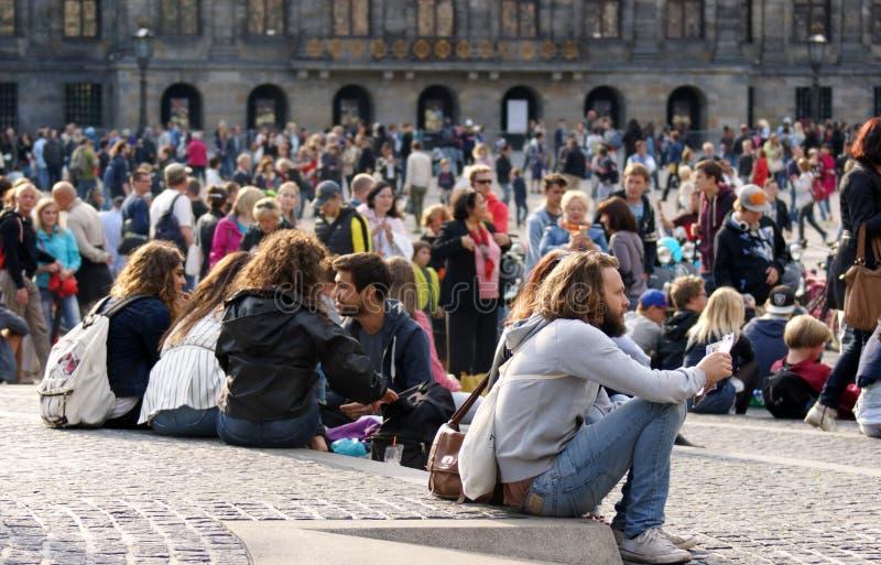 Les touristes rassemblent dans la place de barrage du ` s d'Amsterdam pendant l'été image libre de droits