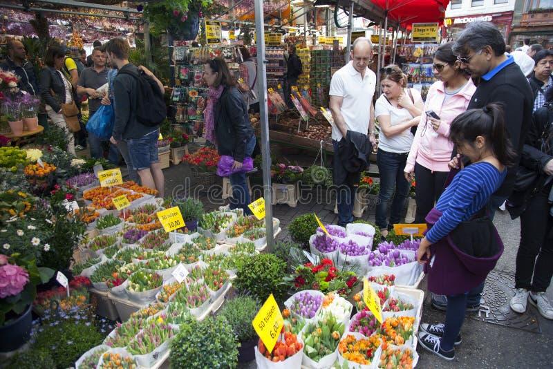Les touristes regardent des marchandises sur le marché de fleur d'Amsterdam photos libres de droits