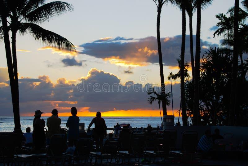 Les touristes silhouettés observent le coucher du soleil au-dessus de la plage d'île photographie stock libre de droits