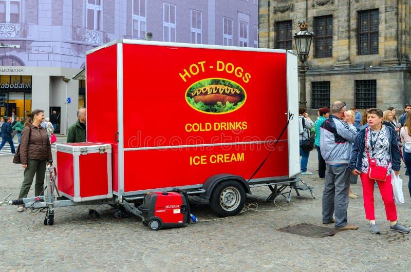 Les touristes sont sur Dam Square près de Royal Palace à Amsterdam, Pays-Bas Fourgon lumineux pour vendre les hot-dogs et les boi image stock