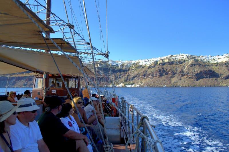 Les touristes sur le bateau après un Santorini passionnant se déclenchent images stock