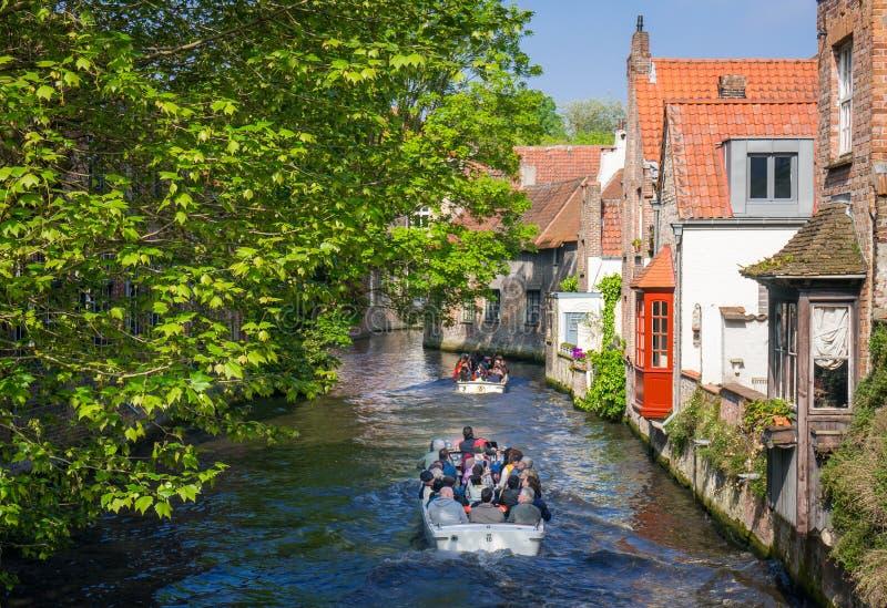 Les touristes sur un bateau de canal voyagent à Bruges image stock