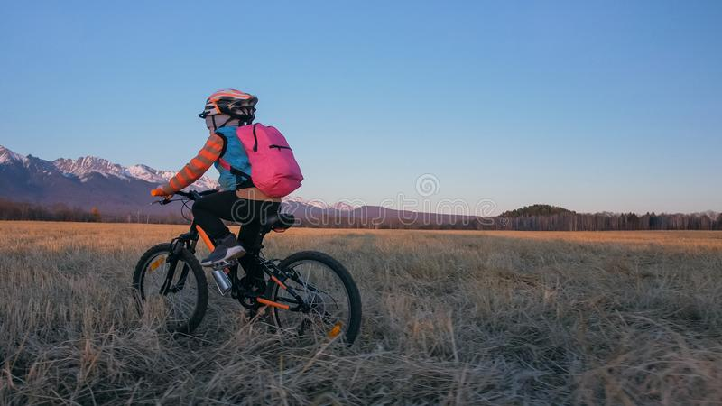 Les tours caucasiens des enfants un font du vélo dans le domaine de blé Cycle orange de noir d'équitation de petite fille sur le  images libres de droits