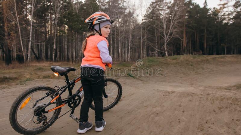 Les tours caucasiens des enfants un font du vélo la voie de route en parc de saleté Cycle orange de noir d'équitation de fille da images stock