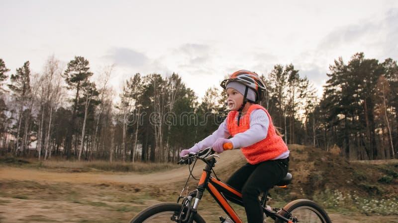 Les tours caucasiens des enfants un font du vélo la voie de route en parc de saleté Cycle orange de noir d'équitation de fille da photographie stock libre de droits