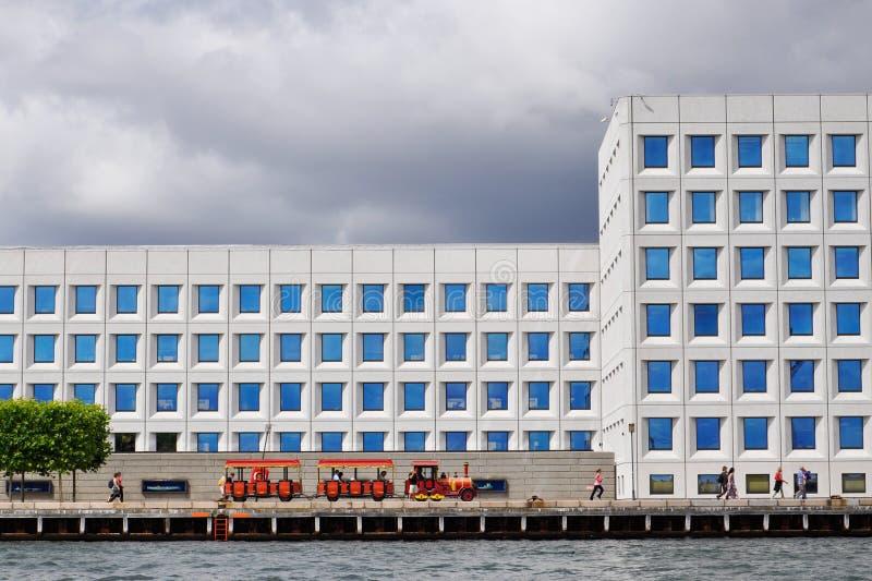 Les trains d'excursion rouges montent le long du bord de mer le long du bâtiment de la plus grande campagne danoise MERSK, Copenh image stock