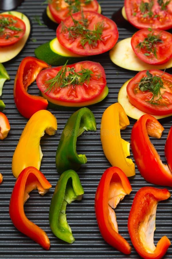 Les tranches de légumes frais sur une casserole de gril apprêtent Foc sélectif image stock