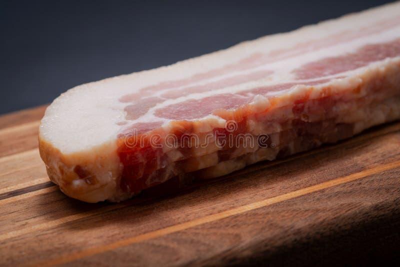 Les tranches de lard d'Apple frais ont fumé le lard disposé sur la planche à découper en bois naturelle photo libre de droits