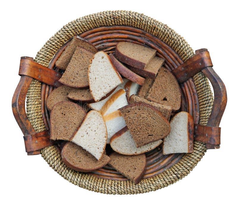 Les tranches de pain noir et blanc dans un panier en bois fait maison ont isolé photos libres de droits