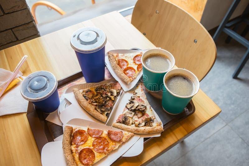 Les tranches de pizza avec le salami et les champignons, café, boit image stock