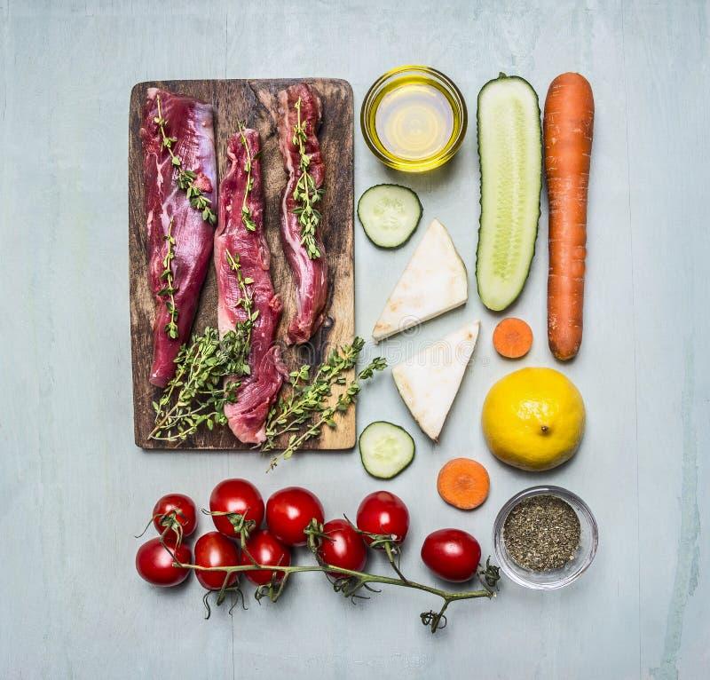 Les tranches fraîches d'agneau cru avec des herbes, des épices, pétrole et citron et des légumes sur la planche à découper ont ra photo libre de droits