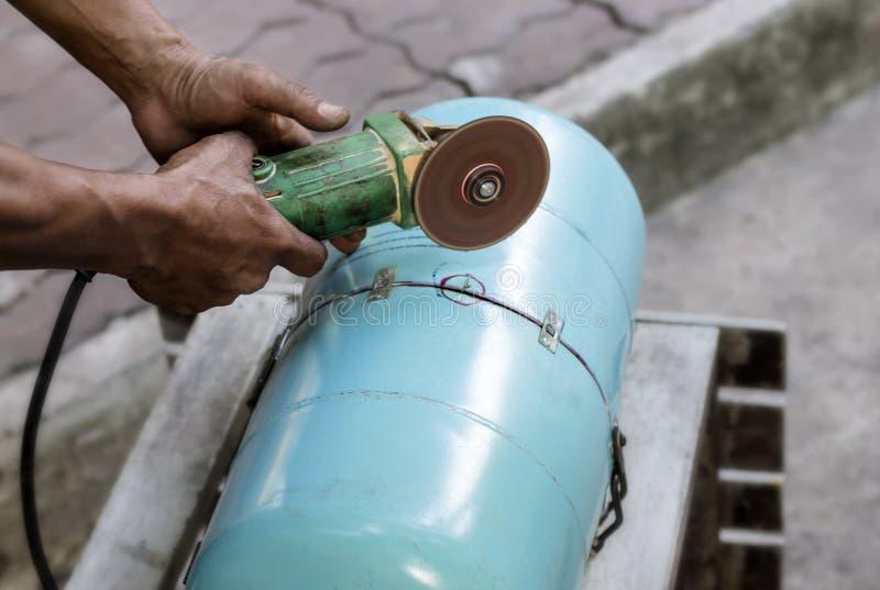 Les travailleurs à l'aide des machines de meulage en métal pour couper des objets ont fait o photos stock