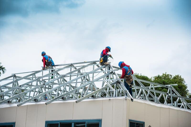 Les travailleurs établissent un cadre en acier de toit sur la haute photos stock
