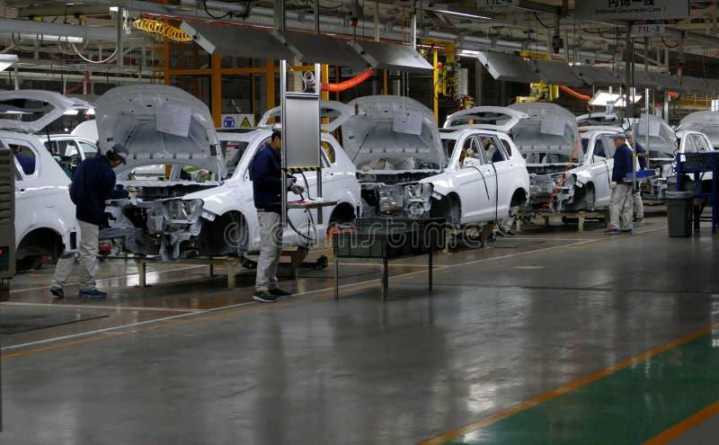 Les travailleurs assemblent une voiture sur la chaîne de montage dans l'usine de voiture images libres de droits