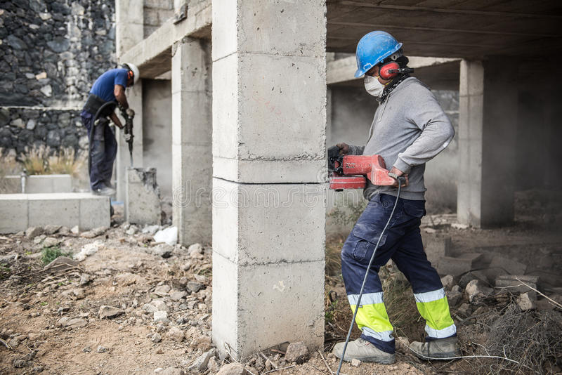 Les travailleurs cassent le béton avec un marteau pneumatique - 2017 image libre de droits