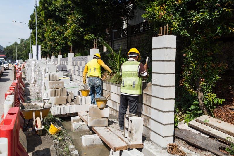 Les travailleurs construisant le bâtiment ébruitent des murs de barrière au highwa occupé image libre de droits