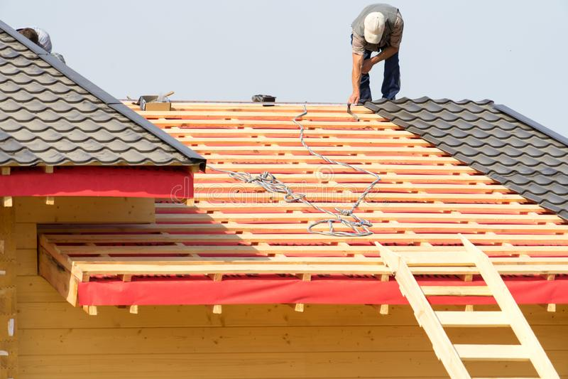 Les travailleurs construisent un toit sur la maison images libres de droits
