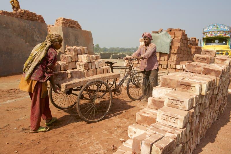 Les travailleurs déplacent des briques à une usine dans Dhaka, Bangladesh photo libre de droits