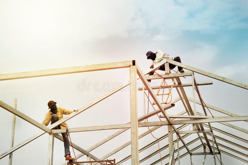 Les travailleurs d'hommes sur la construction en acier de toit structurent l'industrie avec images stock