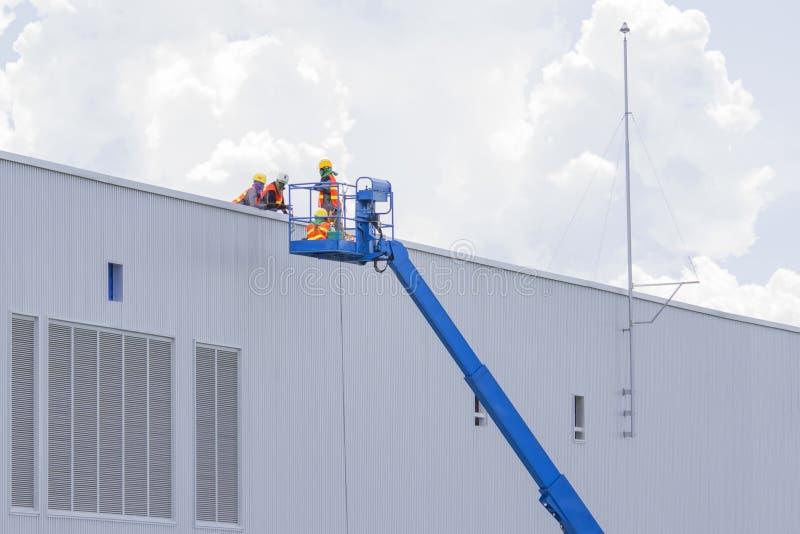 Les travailleurs dans des paniers installent la feuille, construisant une usine photos libres de droits