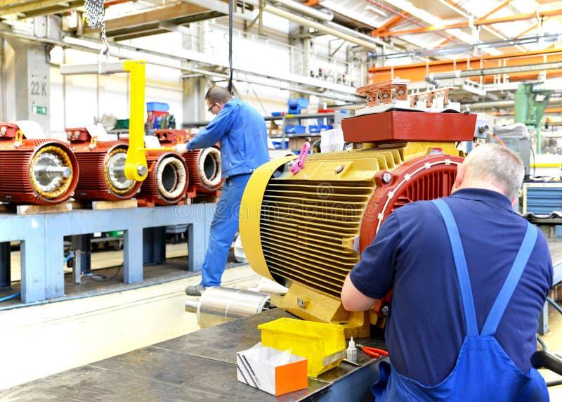 Les travailleurs dans une usine assemblent les moteurs électriques image libre de droits