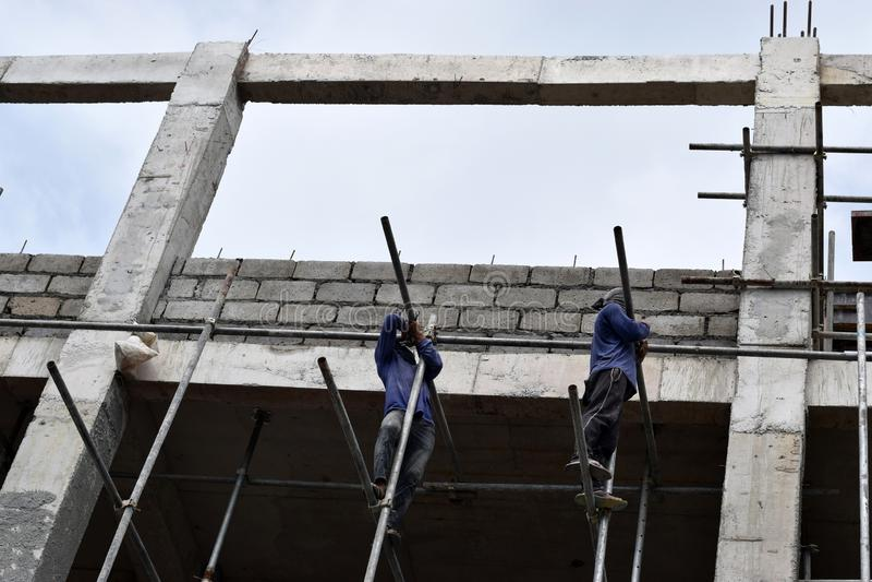 Les travailleurs de la construction philippins installant le métal sifflent des échafaudages sur le gratte-ciel sans tenue de pro image libre de droits