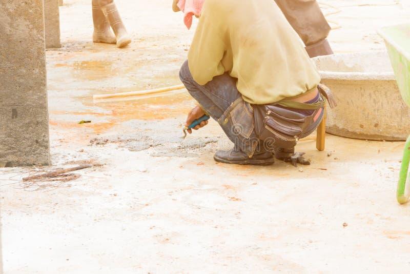 les travailleurs de la construction plâtraient le plancher de réparation dans la construction de lieu de travail une maison photographie stock libre de droits