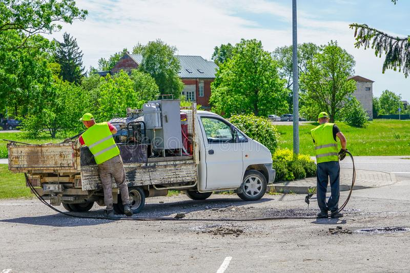 Les travailleurs de route met l'asphalte chaud pour réparer des puits sur la route photographie stock
