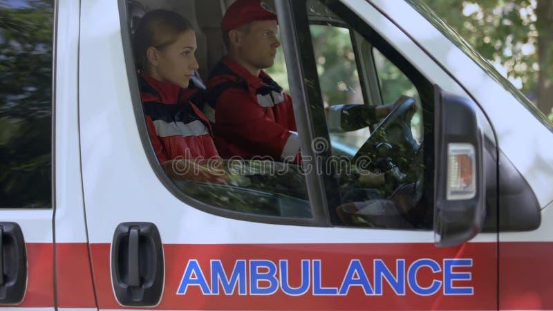 Les travailleurs de secours s'asseyant dans la voiture, conduisant à l'urgence exigent, des premiers secours photos stock