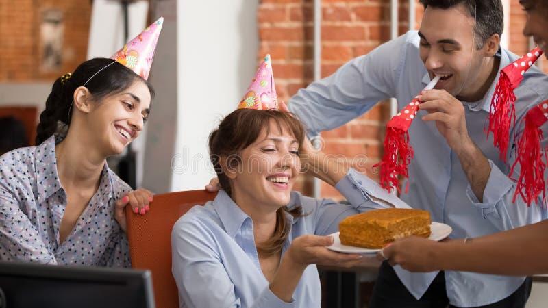Les travailleurs divers excités félicitent le collègue avec l'anniversaire dans le bureau image stock