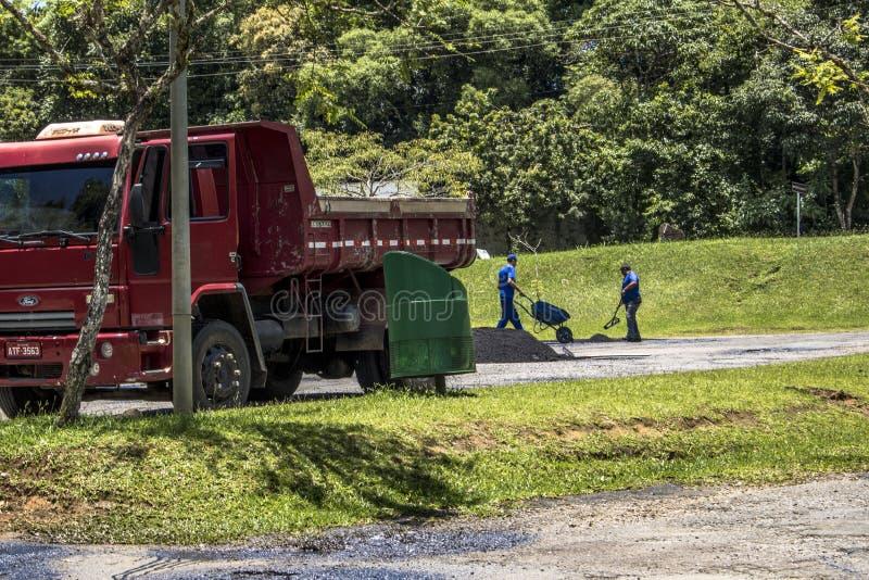 Les travailleurs effectuent l'entretien et couvrent les trous d'une rue dans la ville de Curitiba image libre de droits