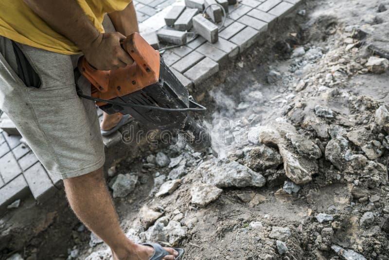 Les travailleurs emploient le briseur concret électrique Travailleur de sexe masculin réparant la surface d'allée avec le marteau photos libres de droits