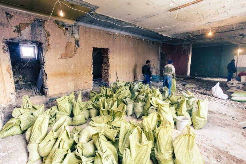 Les travailleurs emportent des déchets de construction et les déchets du démontage dans les sacs pour la disposition dans la cham photos libres de droits