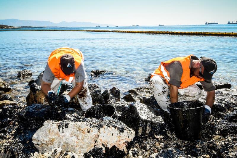 Les travailleurs essayent de nettoyer l'huile qui a lavé à terre, sur une plage o photo stock