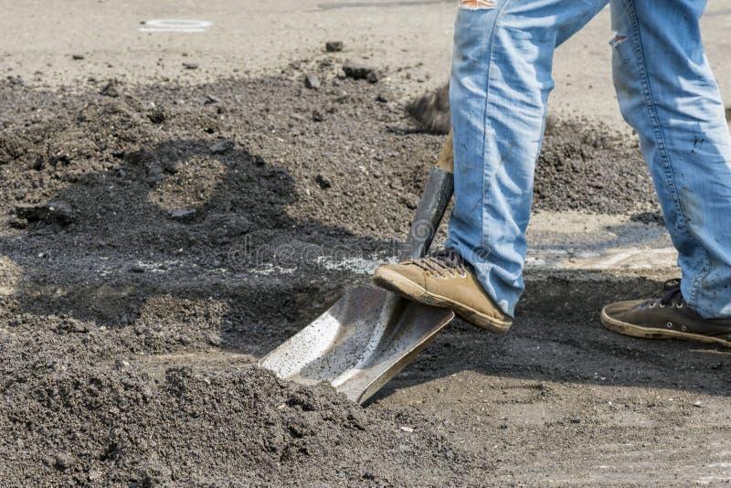 Les travailleurs et les machines travaillent la route pavée avec l'asphalte et le gravier, construction de rue pour le transport  images libres de droits