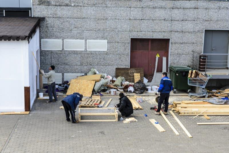 Les travailleurs font trois de quelque chose hors du bois photo libre de droits