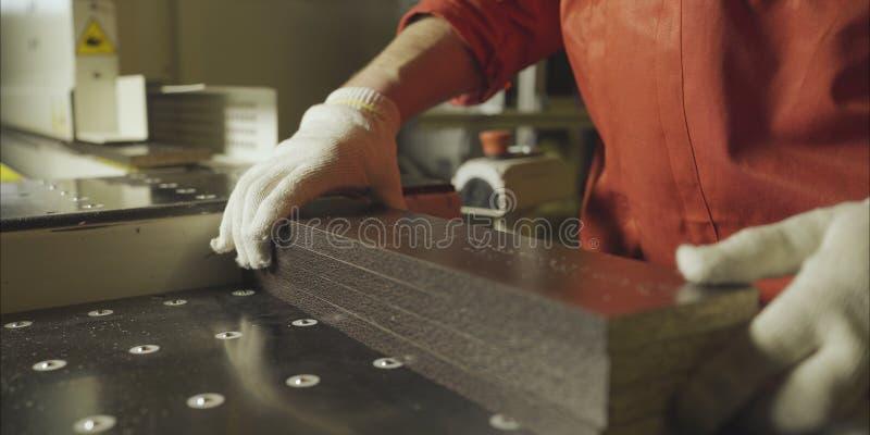 Les travailleurs m?connaissables dans les gants portent les planches en bois le met dans les piles ? la scierie, fin de mouvement photos stock