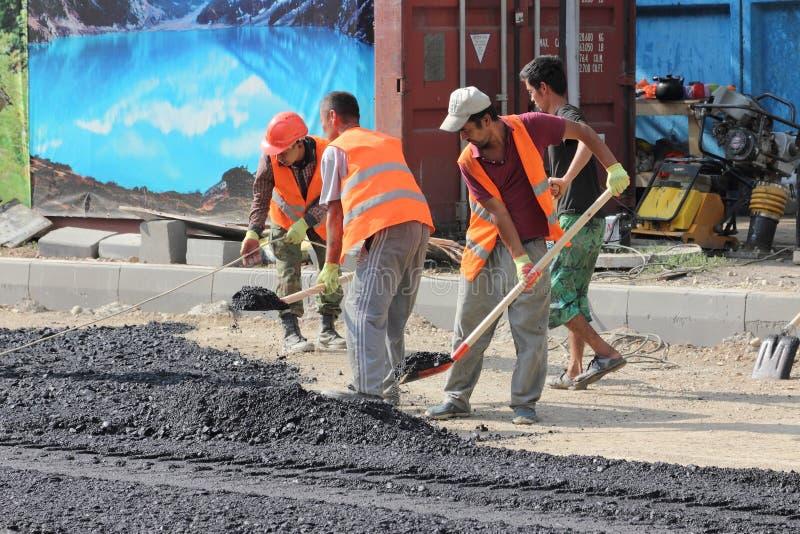 Les travailleurs migrants travaillent à la pose de l'asphalte photo libre de droits