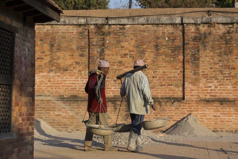 Les travailleurs népalais portant des matériaux pour réparer le tremblement de terre ont endommagé le bâtiment patrimonial photo libre de droits