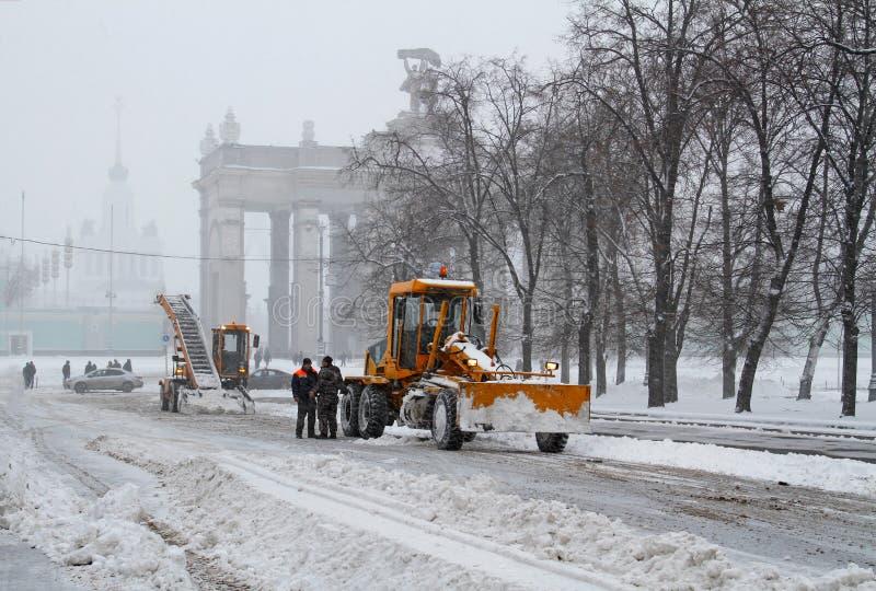 Les travailleurs nettoient de la neige de route près de l'entrée à VDNKh à Moscou photo libre de droits