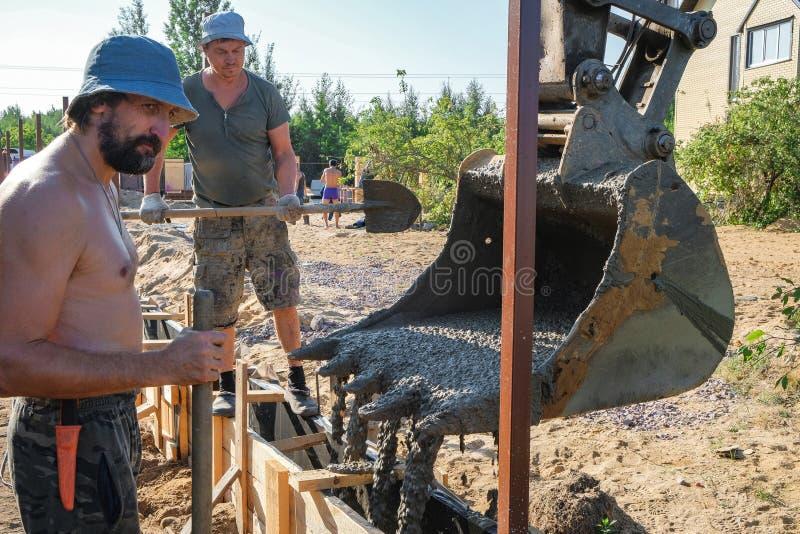 Les travailleurs ont versé le béton dans un coffrage en bois photographie stock