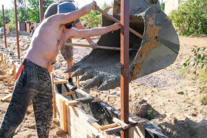 Les travailleurs ont versé le béton dans un coffrage en bois image libre de droits