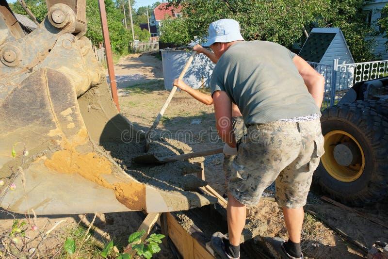 Les travailleurs ont versé le béton dans un coffrage en bois photo libre de droits
