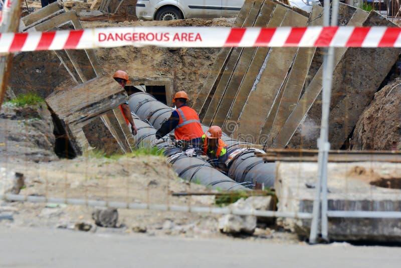 Les travailleurs réparation, installent la canalisation Réparation de l'eau ou des oléoducs, installation Pipes en acier jaunes image stock